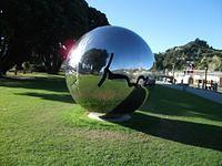 Large shiny sphere on the riverbank.